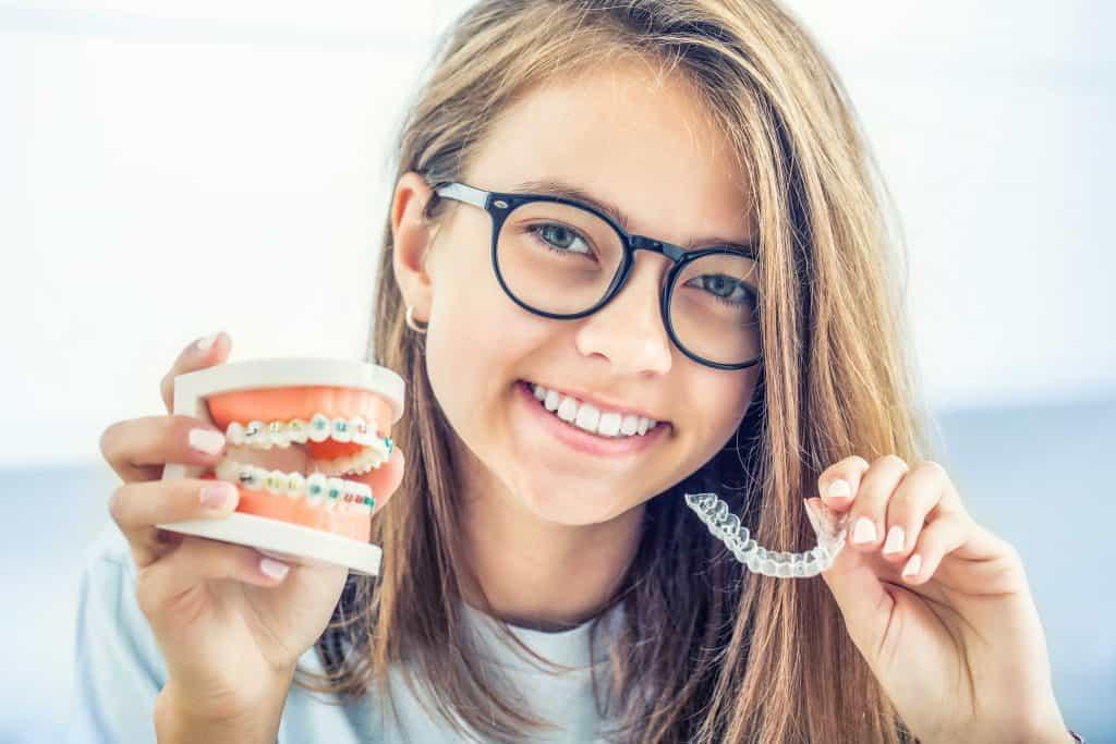 ילדה מציגה גשר שיניים שקוף לעומת גשר שיניים רגיל